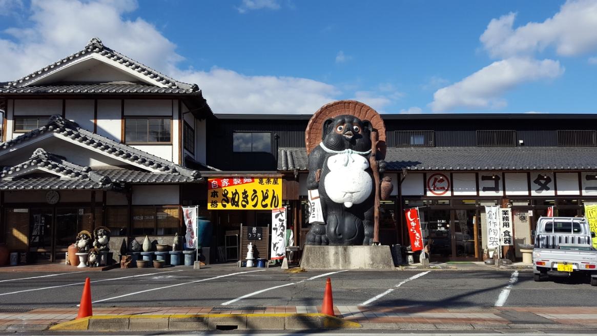 以上で、「本格さぬきうどん 亀楽屋」の御案内となります! こちらのお店は道の両側にお店を出しており、うどんが頂けるのは写真の大きな狸の居ない方ですのでお間違いなく!! タヌキ溢れる信楽の町に来られたら是非とも食べに来られる事をおススメします! 引き継続き、「信楽町の散策」をご覧ください!